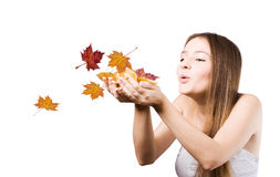 Woman on the autumn leaves blowing Stock Photography