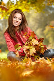 Woman with autumn leaves in hand and fall yellow maple gar Royalty Free Stock Images