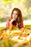 Woman with autumn leaves in hand and fall yellow maple gar Royalty Free Stock Photos