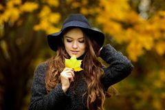 Woman with autumn leaves in hand and fall yellow maple garden background. Young woman with autumn leaves in hand and fall yellow maple garden background Royalty Free Stock Photography