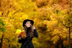 Woman with autumn leaves in hand and fall yellow maple garden background. Young woman with autumn leaves in hand and fall yellow maple garden background Stock Photos