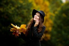 Woman with autumn leaves in hand and fall yellow maple garden background. Young woman with autumn leaves in hand and fall yellow maple garden background Stock Photography
