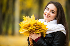 Woman with autumn leaves in hand and fall yellow maple garden background Stock Image