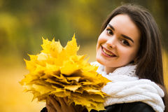 Woman with autumn leaves in hand and fall yellow maple garden background Royalty Free Stock Photos