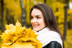 Woman with autumn leaves in hand and fall yellow maple garden background Stock Images