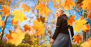 Woman and autumn leaves in the park. Royalty Free Stock Photos