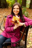 Woman with autumn leaves sitting on bench Stock Image