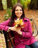 Woman with autumn leaves sitting on bench Royalty Free Stock Photography