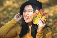 Woman with autumn leaves smiling in sunny park, selective focus. Woman with autumn leaves smiling in sunny park with colorful blurred background outdoors royalty free stock photos