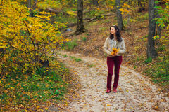 Woman with autumn leaves standing on forest road Stock Photo