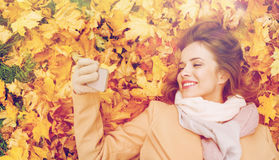 Woman on autumn leaves taking selfie by smartphone Stock Photo