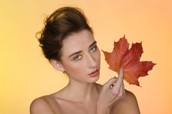 Woman with autumn leaves on yellow background Royalty Free Stock Images