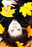 Woman in autumn orange leaves. Young woman in autumn orange leaves stock image