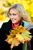 Woman at autumn outdoors. Smiling young attractive woman with autumn maple leaves in park at fall outdoors royalty free stock images