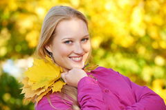 Woman at autumn outdoors. Smiling young attractive woman with autumn maple leaves in park at fall outdoors stock photos