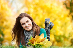 Woman at autumn outdoors. Smiling young attractive woman with autumn maple leaves in park at fall outdoors royalty free stock photos