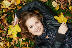 Woman at autumn outdoors. Smiling young attractive woman lying down on autumn maple leaves in park at fall outdoors royalty free stock images