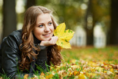 Woman at autumn outdoors. Smiling young attractive woman with autumn maple leaves in park at fall outdoors stock photo