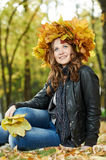 Woman at autumn outdoors. Smiling young attractive woman with autumn maple leaves in park at fall outdoors royalty free stock image