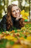 Woman at autumn outdoors. Smiling young attractive woman with autumn maple leaves in park at fall outdoors royalty free stock photography