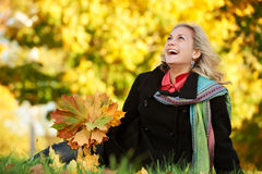 Woman at autumn outdoors. Smiling young attractive woman with autumn maple leaves in park at fall outdoors royalty free stock photo
