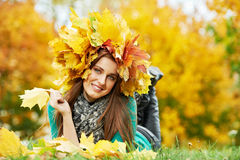 Woman at autumn outdoors. One happy young woman with autumn maple leaves garland lying in park at fall outdoors stock images