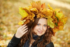 Woman at autumn outdoors. Smiling young attractive woman with autumn maple leaves in park at fall outdoors stock photography