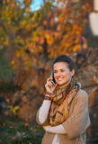 Woman in autumn  outdoors talking cell phone Royalty Free Stock Images