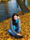 Woman in Autumn Outfit Sitting on Dry Leaves. Pretty Woman in Autumn Outfit Sitting on Dry Leaves Along the Riverside. Looking on Right Side Frame while Hand on stock image
