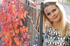 Woman in autumn park. Beautiful blonde smiling, looking at the camera. She walks in autumn park Stock Image
