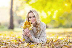 Woman in autumn park. Happy woman lies on dry leaves in autumn park at sunny day Royalty Free Stock Photography