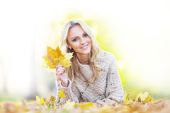 Woman in autumn park. Happy woman lies on dry leaves in autumn park at sunny day Stock Photos