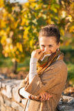 Woman in autumn park hiding behind scarf. Portrait of happy young woman in autumn park hiding behind scarf Royalty Free Stock Photography