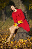 Woman at autumn park hold maple leaves Royalty Free Stock Photos