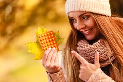 Woman in autumn park holding vitamins medicines Royalty Free Stock Image