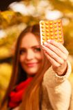 Woman in autumn park holding vitamins medicines Royalty Free Stock Images