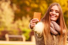 Woman in autumn park holding vitamins medicines Stock Image