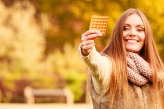 Woman in autumn park holding vitamins medicines Stock Photos