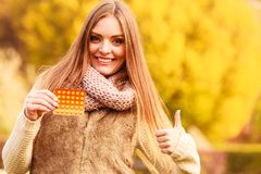 Woman in autumn park holding vitamins medicines. Showing how to deal with seasonal autumnal fever and supporting immunity during cold days Royalty Free Stock Photos