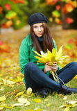 Woman in autumn park holding yellow leaf Royalty Free Stock Photo