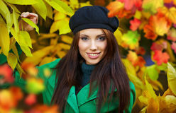 Woman in autumn park holding yellow leaf Stock Image
