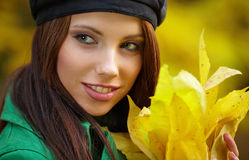 Woman in autumn park holding yellow leaf Stock Photos