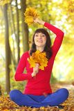 Woman in autumn park with leaves in hand Stock Photography