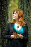 Woman in autumn park. With leaves in hands royalty free stock image