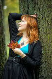 Woman in autumn park. With leaves in hands royalty free stock images