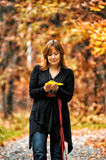 Woman in autumn park. With leaves in hands stock image