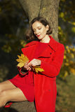 Woman at autumn park look at leaves Royalty Free Stock Photography