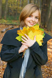 Woman in autumn park with maple leaves Stock Photo