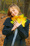 Woman in autumn park with maple leaves Royalty Free Stock Photography