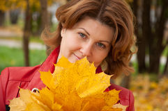Woman in autumn park with a maple leaves Stock Images